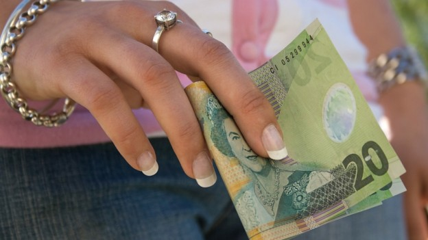 A woman uses a NZ$20 note
